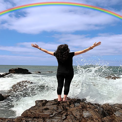 a woman raising her arms to a rainbow in the sky