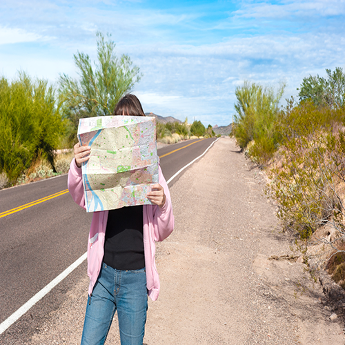 A woman standing along side a remote deserted road reading a map.